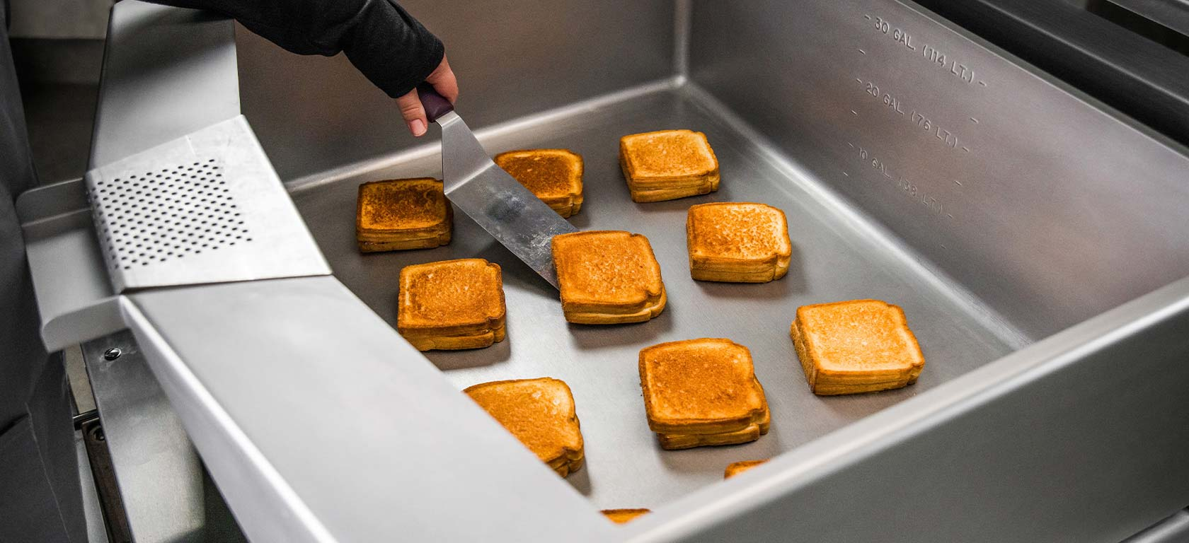 Grilled cheese being cooked on a braising pan.