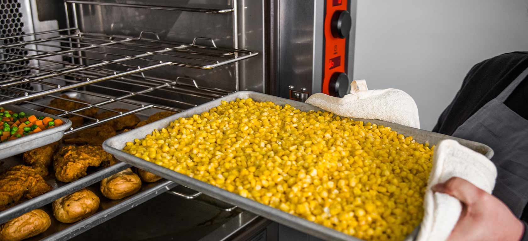 Vulcan Convection Oven being loaded with corn kernels on an aluminum tray.