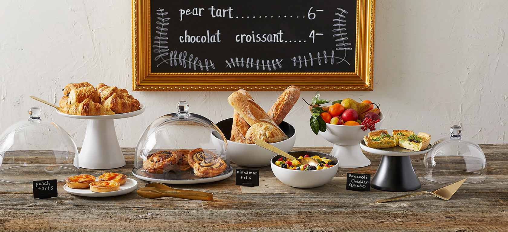 Array of bakery dishes like bowls and glass displays, containing an array of baked goods.