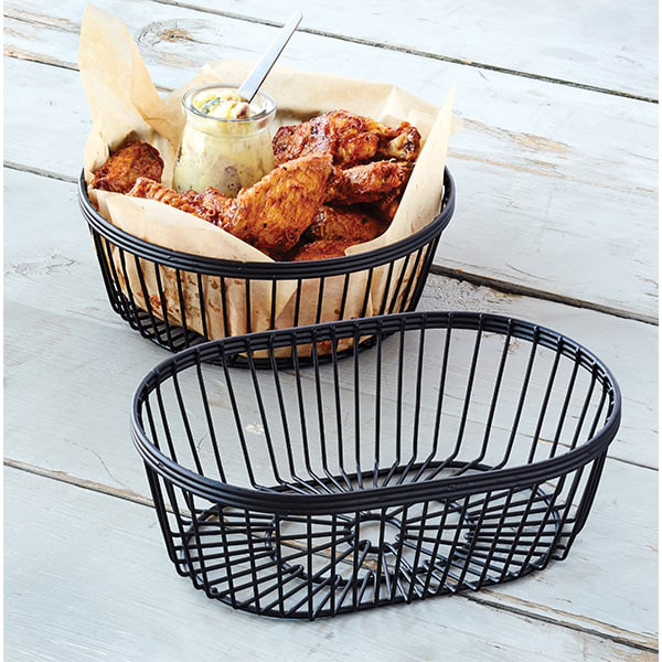 Two black metal baskets, the furthest one holds fried chicken wings and dressing.