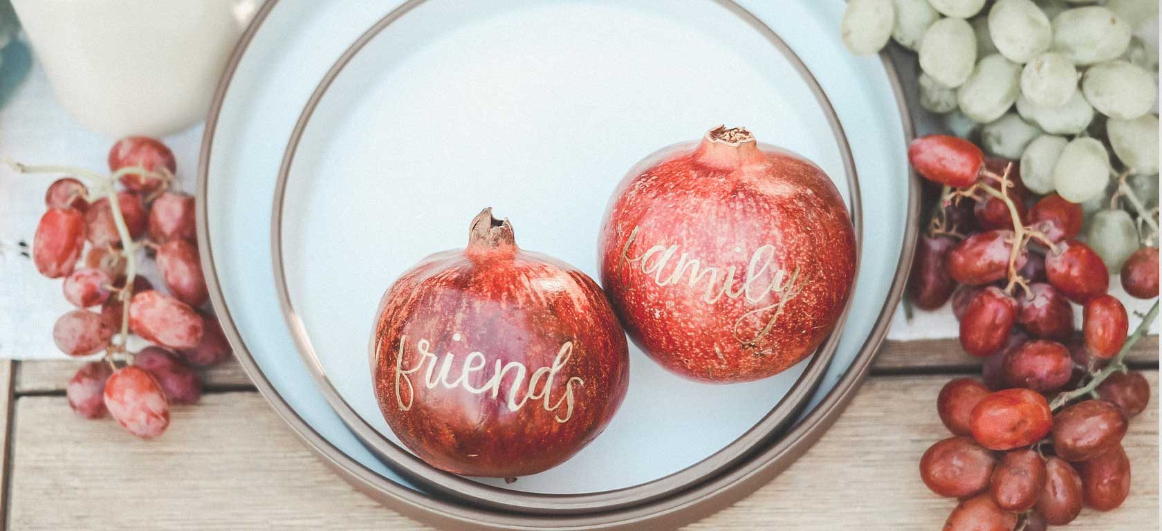 Elegant gold-trimmed plate holding tender pomegranates with the words friends and family on them.