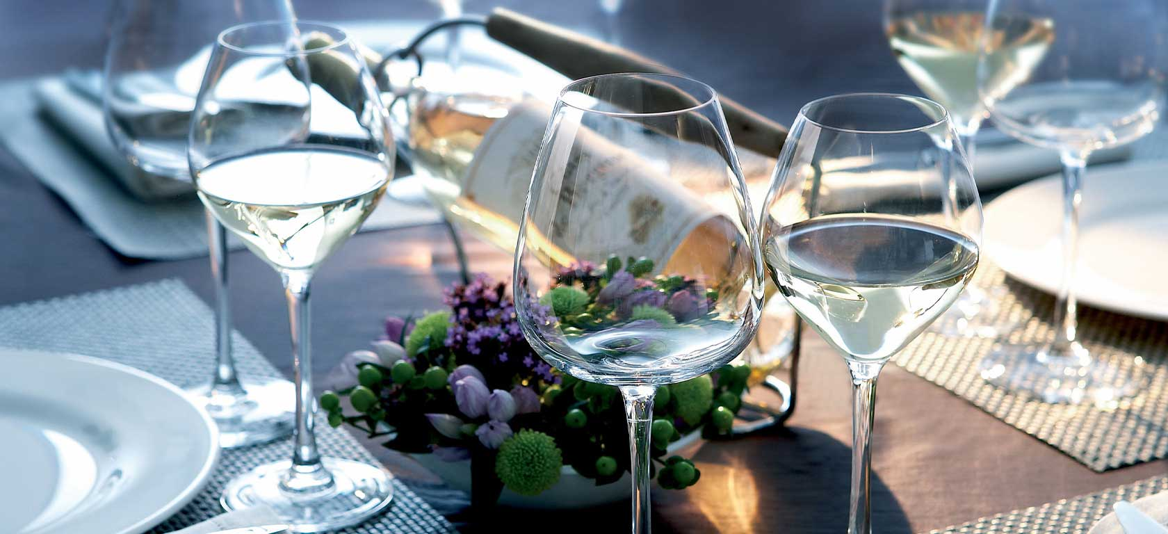 Delicate looking empty wine glasses in a tastefully decorated table.