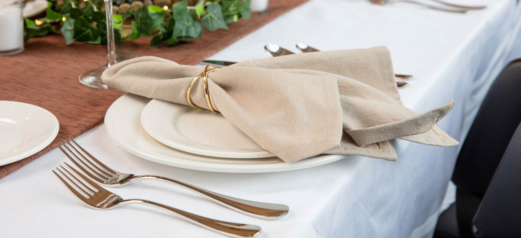 Elegant beige cloth napkin in golden napkin ring sitting on ornate table.