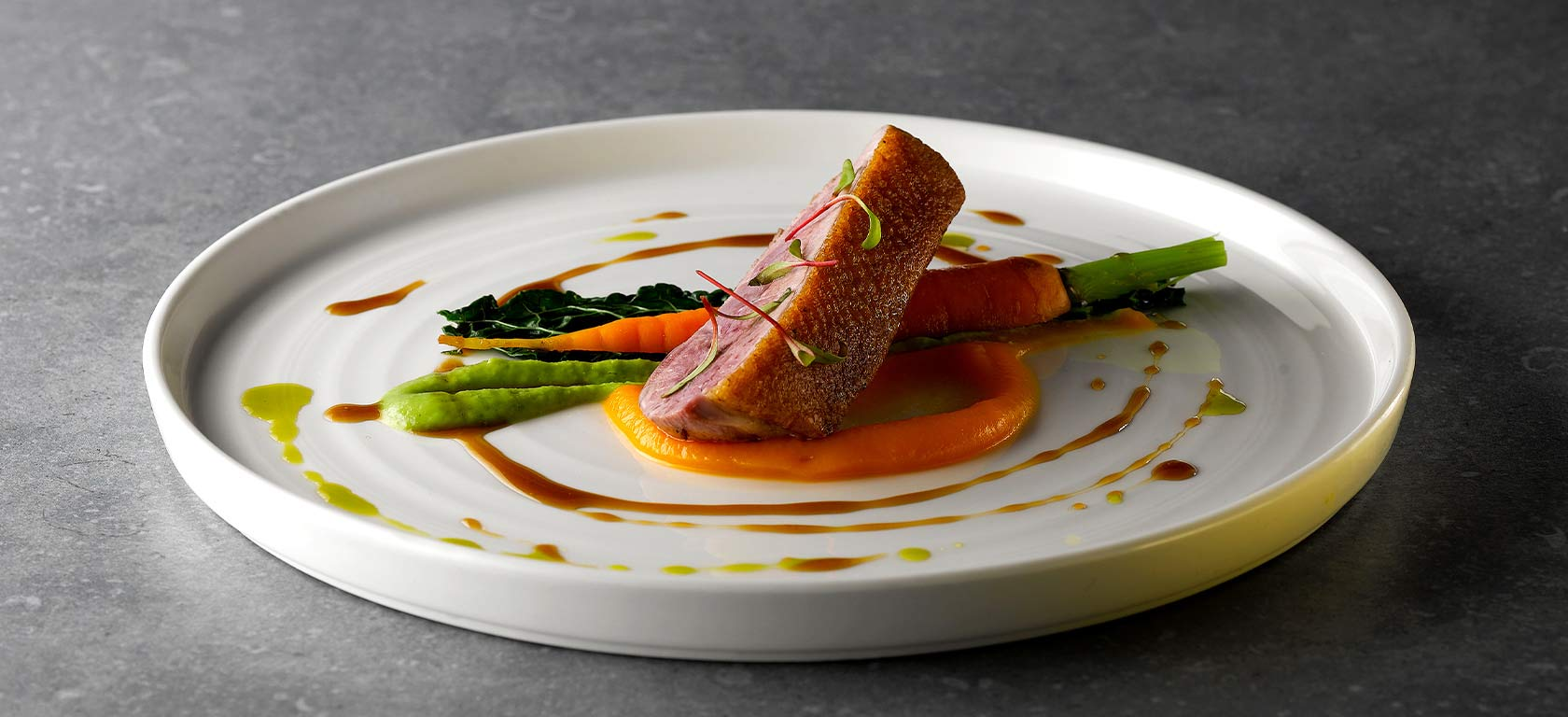Tender salmon and asparagus plated delicately over an elegant white ceramic plate.