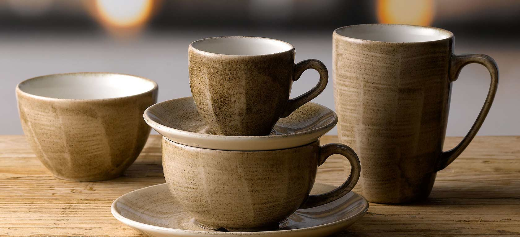 Rustic earth-toned saucers and mugs with angular features.