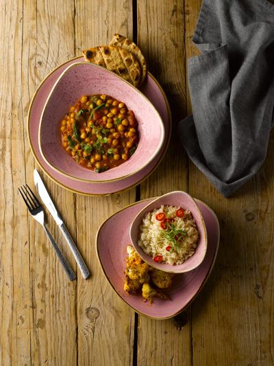 Blush-toned asymmetrical plates and bowls containing a Mediterranean meal.