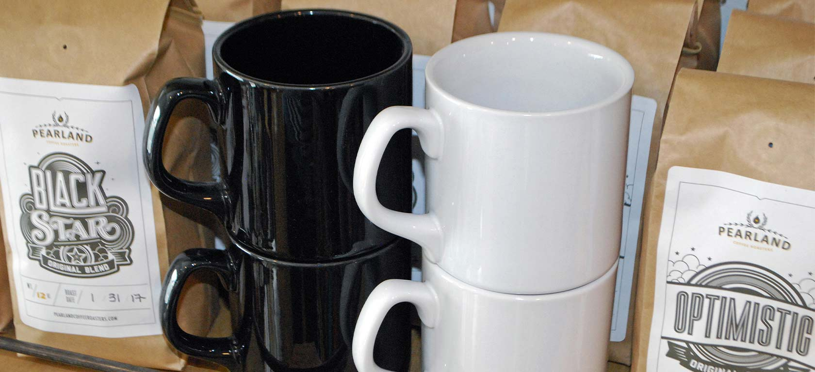 Ceramic black and white mugs displayed between two bags of coffee beans.