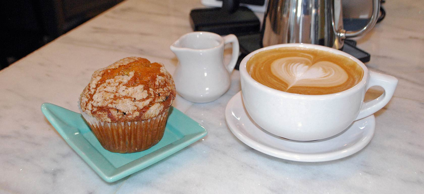 Ceramic coffee mug accompanied by an appetizing muffin on a curious green ceramic holder