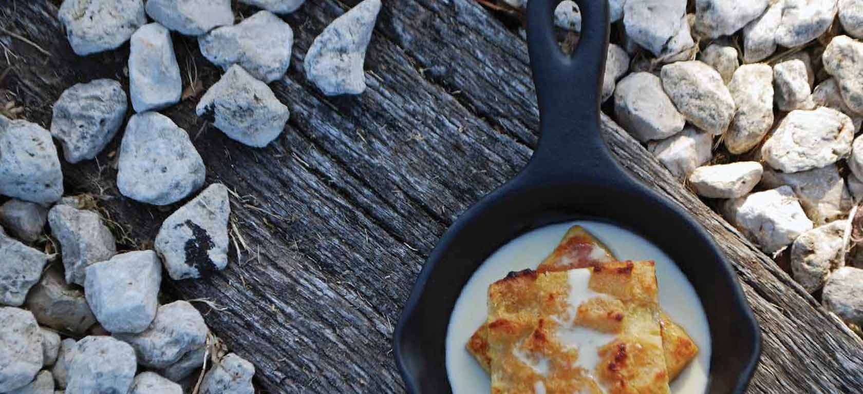 Black ceramic skillet with appetizing meal sitting on a wooden, rustic looking setting.