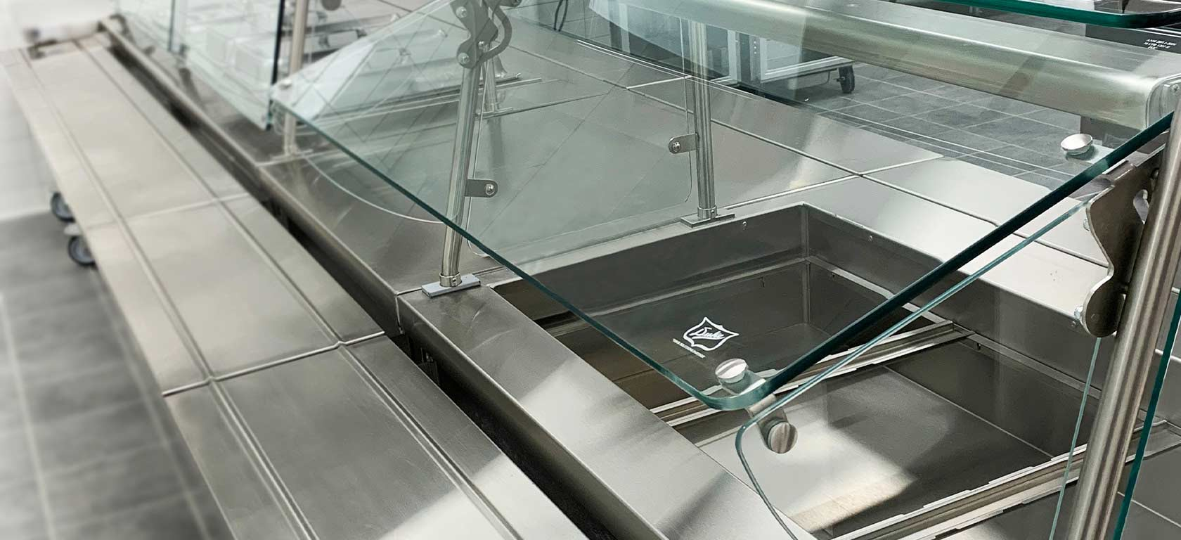 Vertical shot of glass cover on a stainless steel food display for a cafeteria.