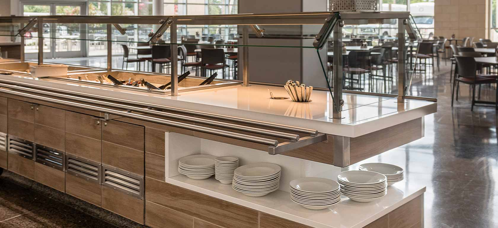 Close-up shot of earth-toned buffet food display with white trim.