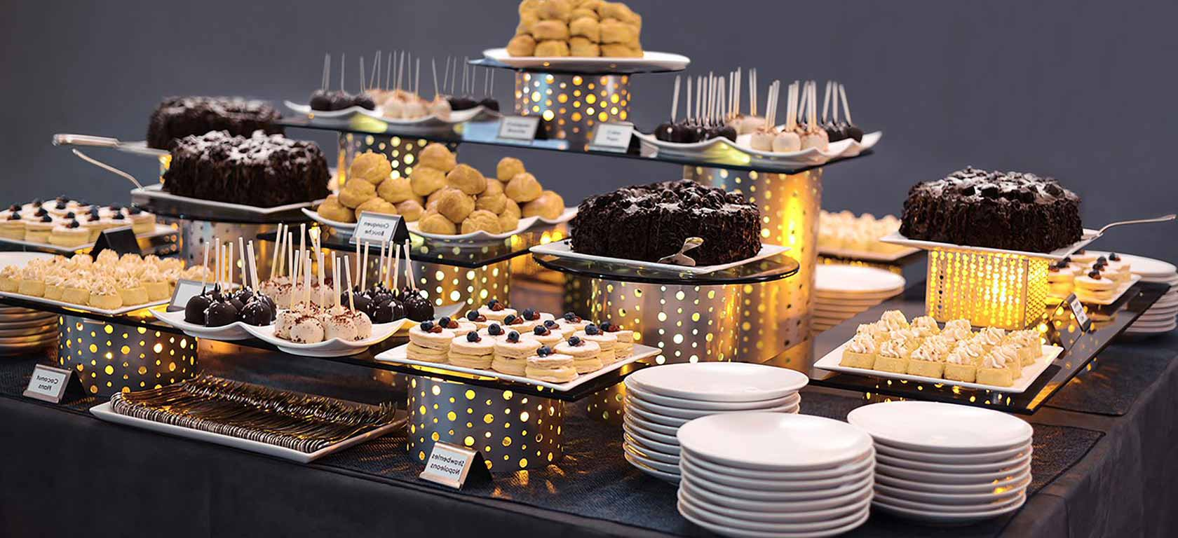 Buffet array of deserts on chrome utensils and risers.