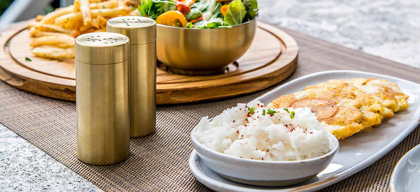 White round ceramic tableware on table accompanied by golden salt and pepper shakers