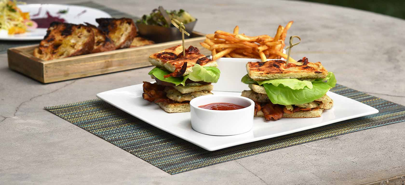 Sandwich and fries arranged on simplistic white ceramic plates.