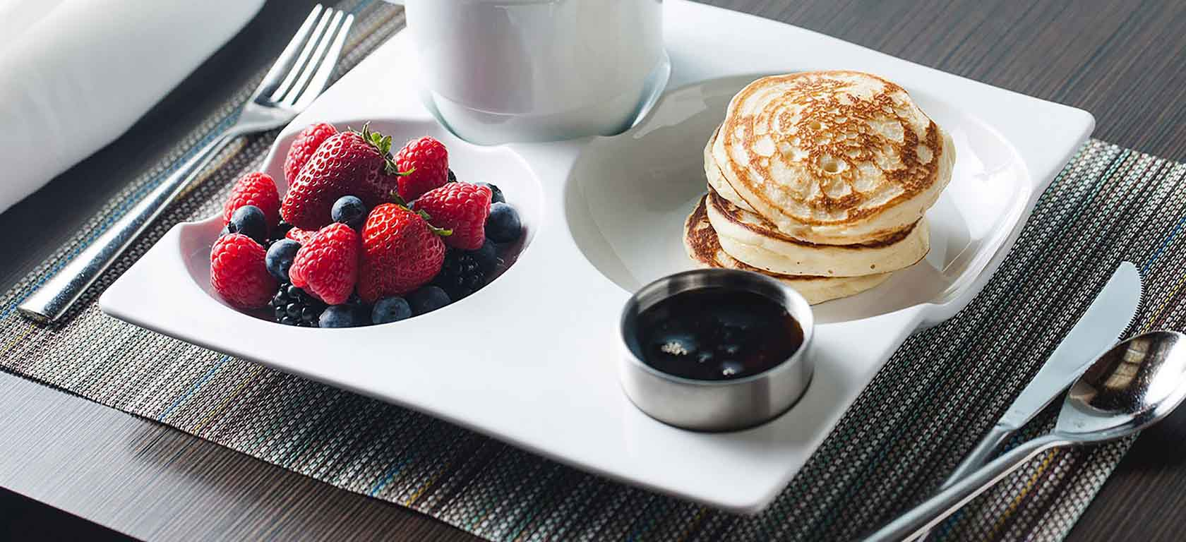 Intricate undulated white ceramic dish holding a pancakes and fruit breakfast.