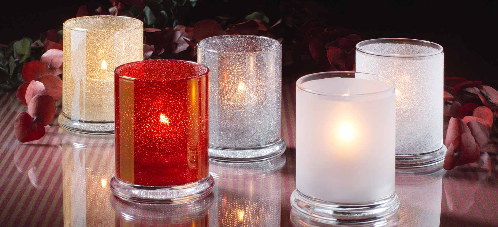Frosted glass candle holders containing homely burning candles.