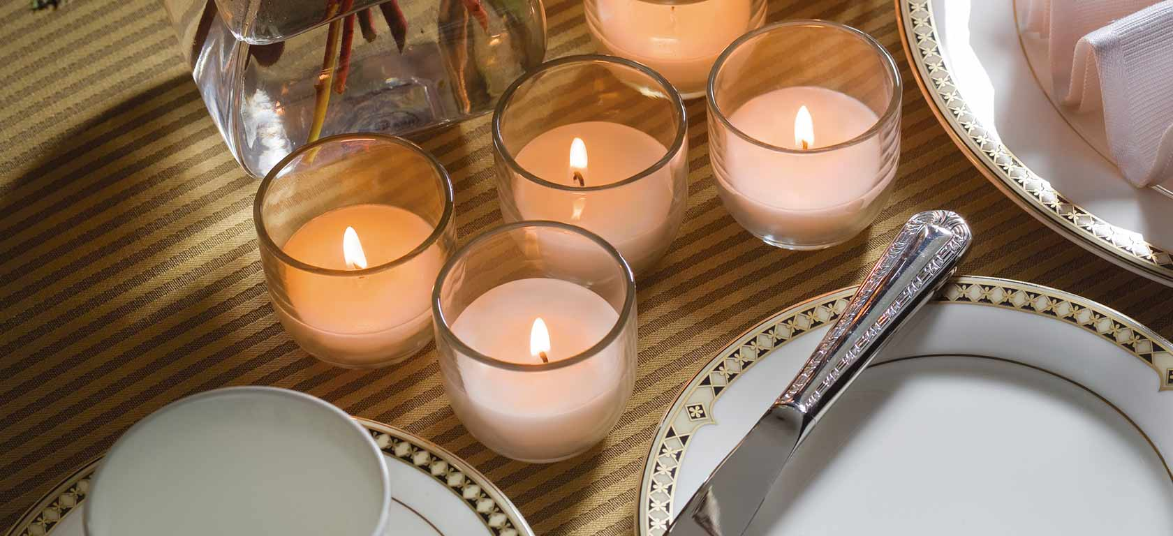 Delicate glass votives glowing warmly.