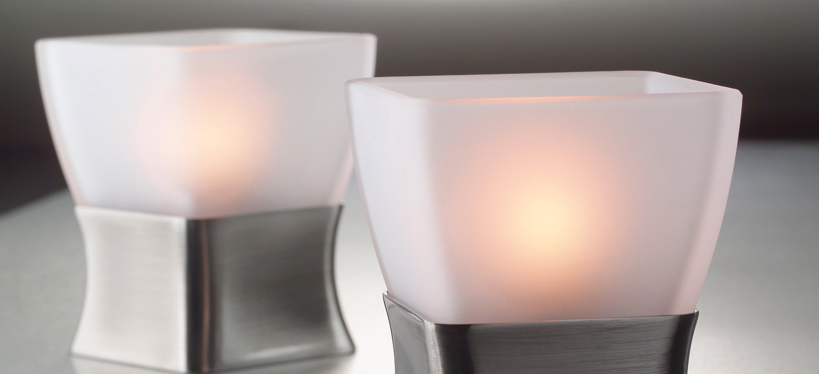 White frosted glass candle holders in a tapered square shape.