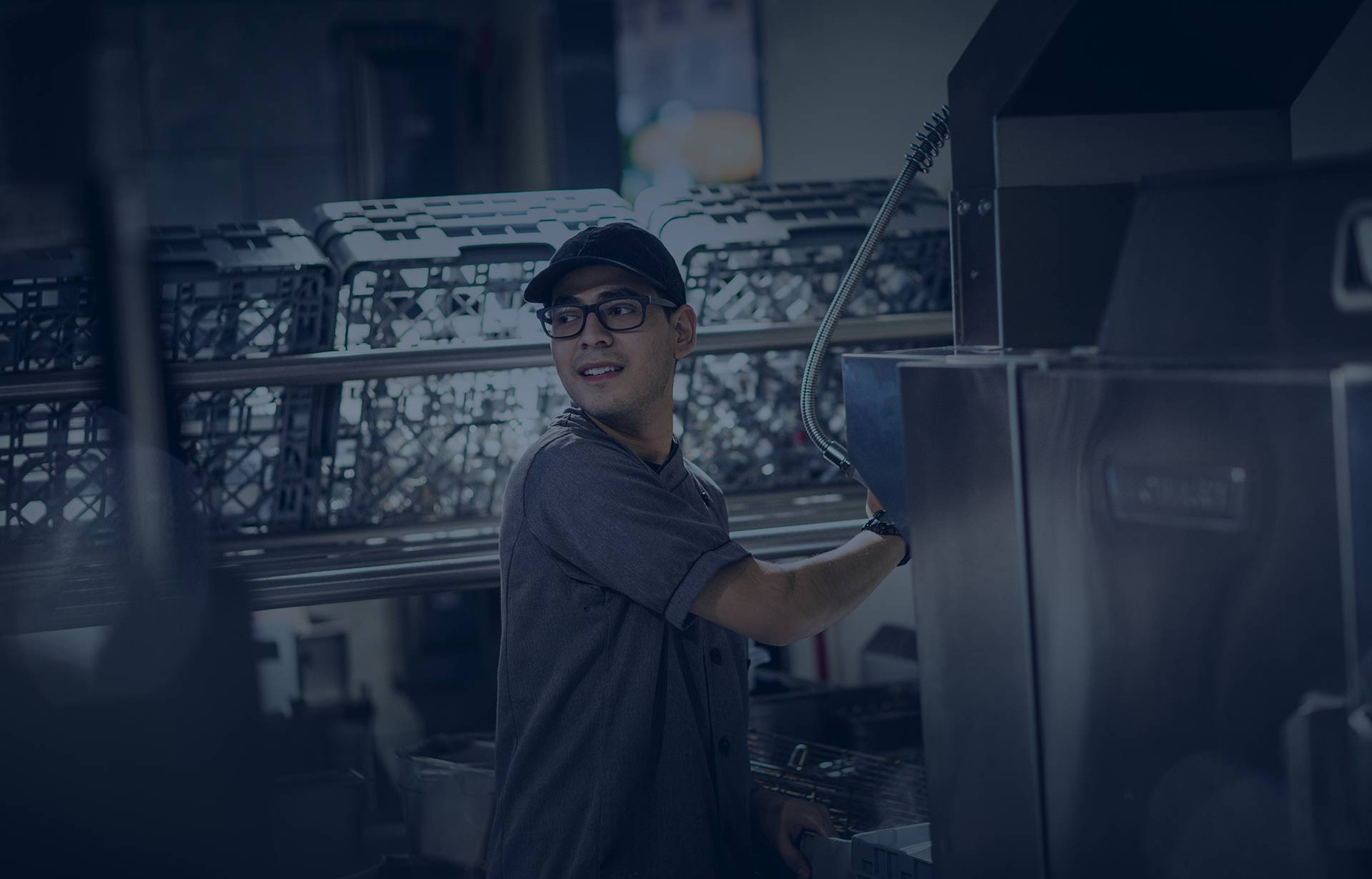 Active kitchen worker in hat and glasses multi-tasking.