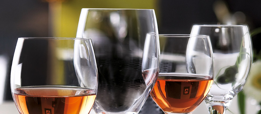 Close up view of four wine glasses, two of which are partially filled with amber liquid.