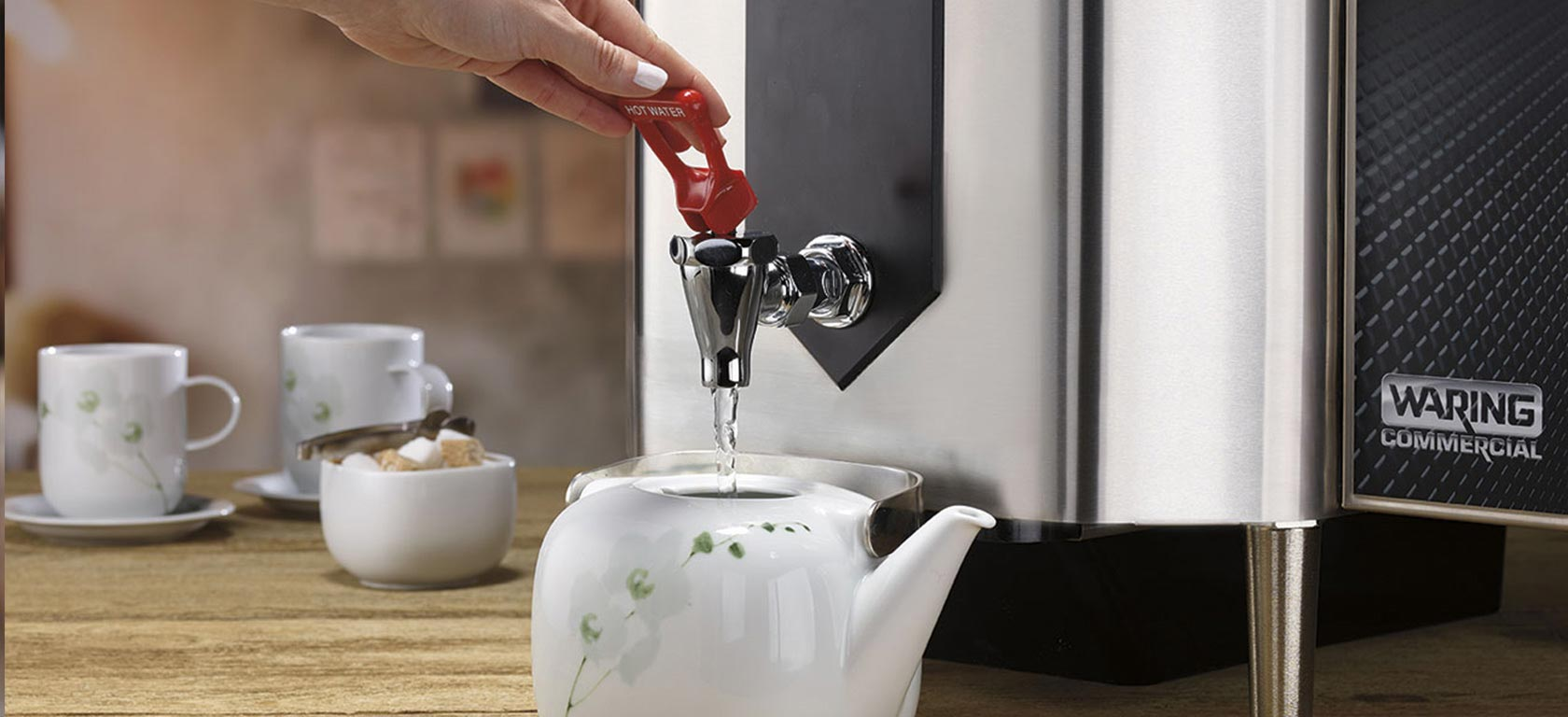 Chrome-finished Waring coffee maker pours hot water into a ceramic teapot.