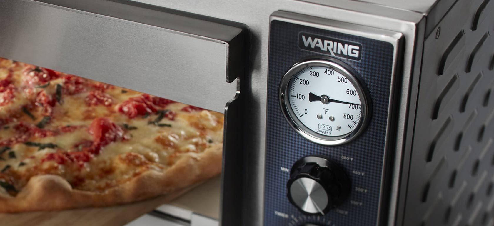 Waring toaster oven with chrome finish warming a flatbread.