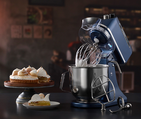 Waring Commercial blue-tinged chrome finish electric mixer surrounded by an assortment of baked goods.