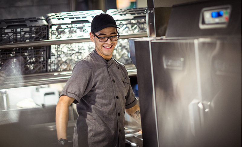 Kitchen worker with glasses in gray shirt smiles as he works with some kitchen equipment.