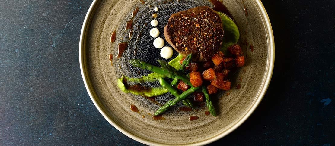 Delicious steak and greens arrangement on round brown ceramic dish.