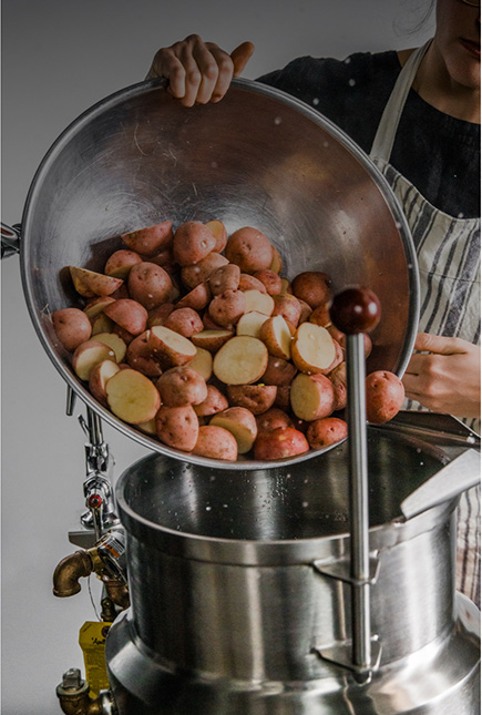 Kitchen line worker pours sliced potatoes to a large stainless steel pot.