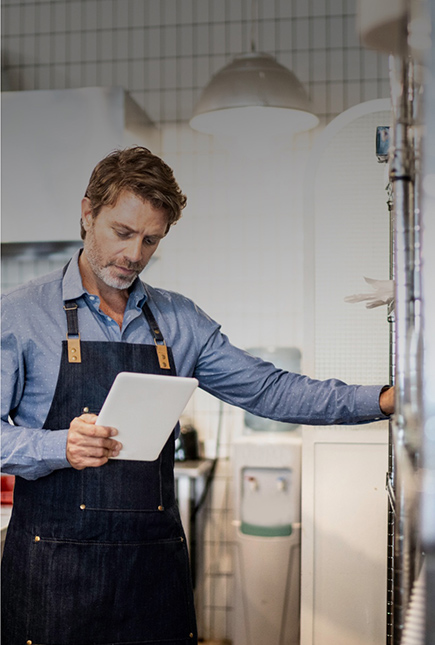 Apron-clad kitchen worker in a blue shirt glances at document in hand before opening a stainless steel door.