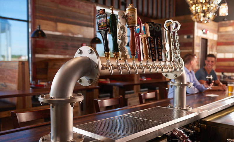 Assortment of beer taps in a rustic bar setting.