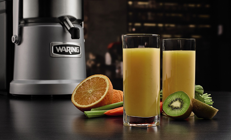 Dull chrome-finished Waring juicer in the background, two tall glasses of freshly squeezed orange and kiwi juice in the foreground.