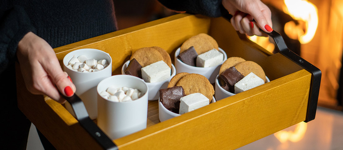 Minimalist golden brown wooden tray holding array of elegant mugs filled with smores.